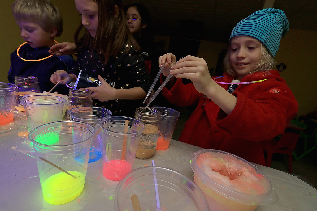 . Stevens Memorial Library held a Glow Party on Wednesday night in their Activity Room for kids 5-12. The kids mixed baby oil with glow in the dark paint and water during the event. Atherton Conklin, 8, plays with the mixtures. SENTINEL & ENTERPRISE/JOHN LOVE