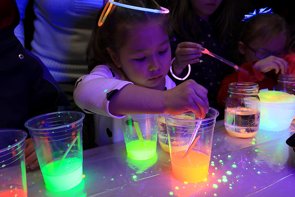 . Stevens Memorial Library held a Glow Party on Wednesday night in their Activity Room for kids 5-12. The kids mixed baby oil with glow in the dark paint and water during the event. Lavinia Vine,5, plays with the mixtures. SENTINEL & ENTERPRISE/JOHN LOVE