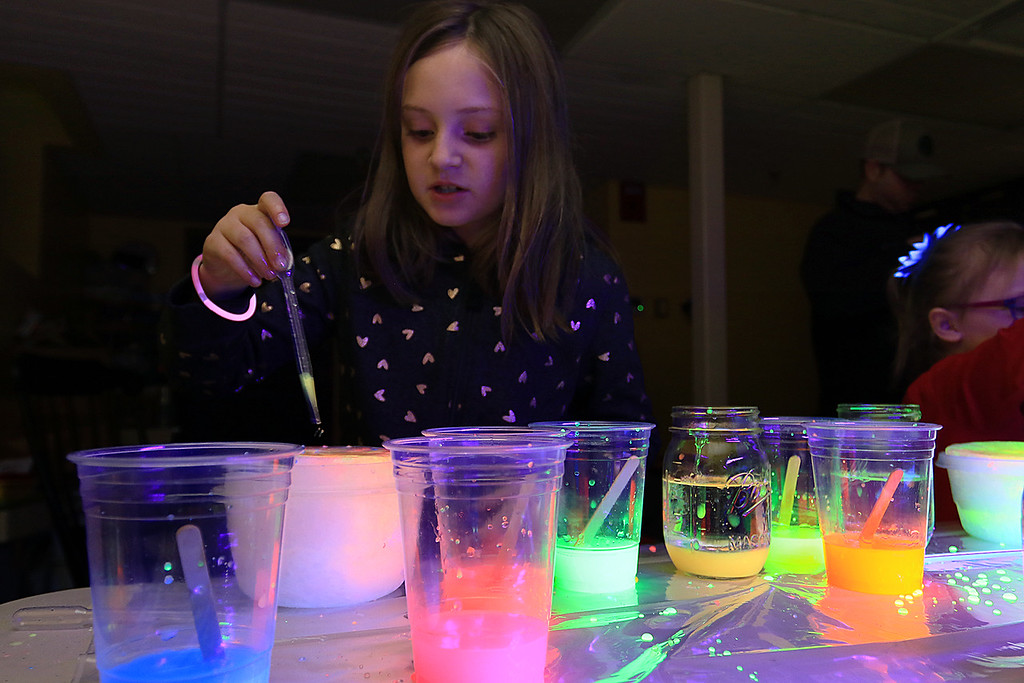 . Stevens Memorial Library held a Glow Party on Wednesday night in their Activity Room for kids 5-12. The kids mixed baby oil with glow in the dark paint and water during the event. Evelyn Holmes, 8, plays with the mixtures. SENTINEL & ENTERPRISE/JOHN LOVE