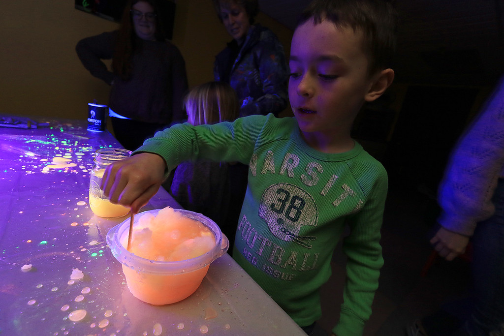 . Stevens Memorial Library held a Glow Party on Wednesday night in their Activity Room for kids 5-12. The kids mixed baby oil with glow in the dark paint and water during the event. Fisher Davis, 6, plays with the mixtures. SENTINEL & ENTERPRISE/JOHN LOVE