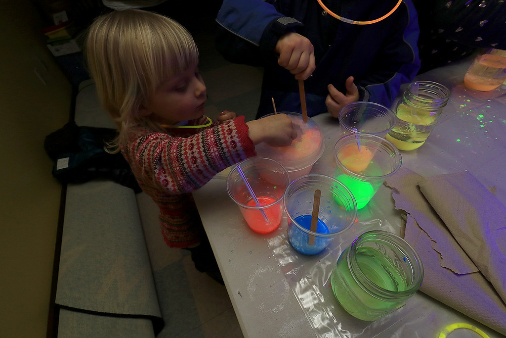 . Stevens Memorial Library held a Glow Party on Wednesday night in their Activity Room for kids 5-12. The kids mixed baby oil with glow in the dark paint and water during the event. Alice Branham, 3, plays with the mixtures. SENTINEL & ENTERPRISE/JOHN LOVE