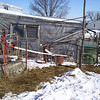 "(7 of 10) Pump and pipe to fill Solar Stock Tank<br /> Several years ago I enclosed an old bathtub in glass to make a solar stock tank for the goats to have water that's not to hard to drink in the winter time. The back of the barn is facing to the South-east so it catches the sun from the time it comes up to when it goes down. It can be 0°F and by 9 or 10 o'clock it will be thawing around the edges inside. I do have to chop out some ice but then it will keep it open so they can drink. When it is cloudy for a week at a time it don't work to well but when the sun shines it is great, You've heard of ""a bull in a china closet"", Well a Billy in a glass house is about as bad. That is why I have the cattle panel out from the glass side, to keep the Billie's away from the glass, The end is from a bank window, about 1 ¼"" thick, they can't hurt that. The glass I had was longer than the tub so I put wool at the end that the cats go in to lie on and warm up in the sun shine. The pipe going in is in line with the pump on the South-west side of the barn, I use that to keep it full. The snow on top will pretty well melt off in 1 or 2 days of sunshine"