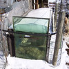 "(4 of 10) Solar Stock Tank End Thawed<br /> Several years ago I enclosed an old bathtub in glass to make a solar stock tank for the goats to have water that's not to hard to drink in the winter time. The back of the barn is facing to the South-east so it catches the sun from the time it comes up to when it goes down. It can be 0°F and by 9 or 10 o'clock it will be thawing around the edges inside. I do have to chop out some ice but then it will keep it open so they can drink. When it is cloudy for a week at a time it don't work to well but when the sun shines it is great, You've heard of ""a bull in a china closet"", Well a Billy in a glass house is about as bad. That is why I have the cattle panel out from the glass side, to keep the Billie's away from the glass, The end is from a bank window, about 1 ¼"" thick, they can't hurt that. The glass I had was longer than the tub so I put wool at the end that the cats go in to lie on and warm up in the sun shine. The pipe going in is in line with the pump on the South-west side of the barn, I use that to keep it full. The snow on top will pretty well melt off in 1 or 2 days of sunshine"