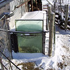 "(3 of 10) Solar Stock Tank End Frosted<br /> Several years ago I enclosed an old bathtub in glass to make a solar stock tank for the goats to have water that's not to hard to drink in the winter time. The back of the barn is facing to the South-east so it catches the sun from the time it comes up to when it goes down. It can be 0°F and by 9 or 10 o'clock it will be thawing around the edges inside. I do have to chop out some ice but then it will keep it open so they can drink. When it is cloudy for a week at a time it don't work to well but when the sun shines it is great, You've heard of ""a bull in a china closet"", Well a Billy in a glass house is about as bad. That is why I have the cattle panel out from the glass side, to keep the Billie's away from the glass, The end is from a bank window, about 1 ¼"" thick, they can't hurt that. The glass I had was longer than the tub so I put wool at the end that the cats go in to lie on and warm up in the sun shine. The pipe going in is in line with the pump on the South-west side of the barn, I use that to keep it full. The snow on top will pretty well melt off in 1 or 2 days of sunshine"