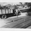 P00064 Sailor in work uniform leaning on truck on dock