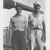 "P00139 Two sailors in work uniform standing on main deck in front of 5"" gun barrel"