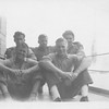 P00138 Five sailors in work uniforms seated on main deck