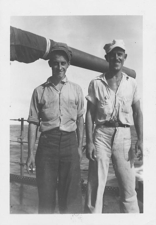"P00139 Two sailors in work uniform standing on main deck in front of 5"" gun barrel"