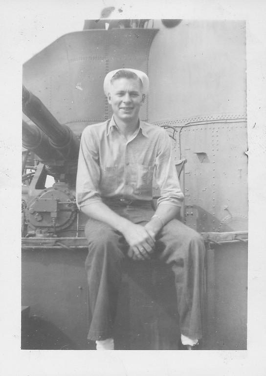 "P00136 Sailor seated on 3"" gun mount in work uniform"