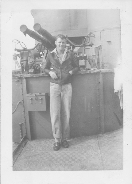 "P00152 Sailor in civiian clothes on deck in front of 3"" gun mount"
