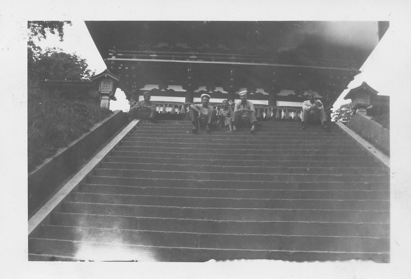 P00142 Two sailors in work uniform sitting on temple steps with Japanese local (probably 1945)