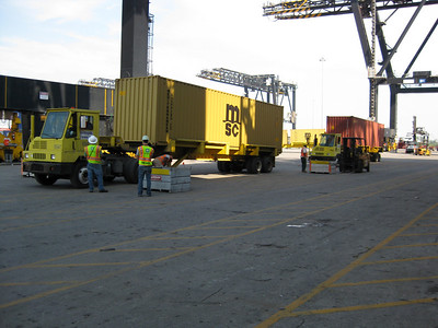 Trucks bringing containers alongside for loading