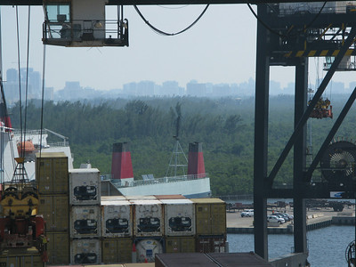 Crane lowering a container into place with Dahia state park and Miami hirises in the background