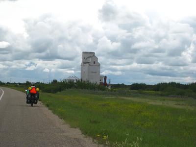 Scott riding toward a grain elevator