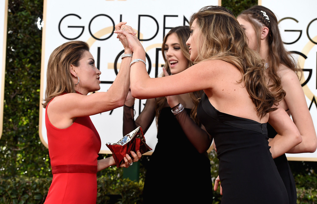 . Kit Hoover, left, greets Miss Golden Globes, Sistine Stallone, from second left, Scarlet Stallone and Sophia Stallone as they arrive at the 74th annual Golden Globe Awards at the Beverly Hilton Hotel on Sunday, Jan. 8, 2017, in Beverly Hills, Calif. (Photo by Jordan Strauss/Invision/AP)