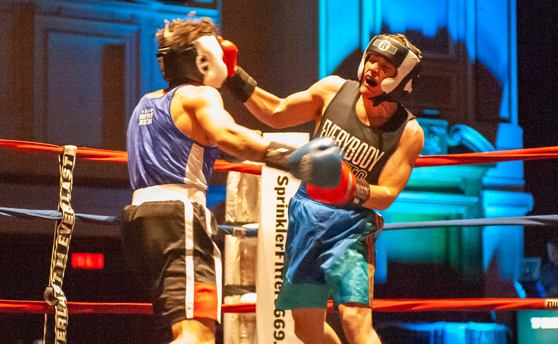 Carl Gustafson (blue trunks), of Boston, battles <br /> Omar Riaz (black trunks), of Boston, during Thursday Golden Golves match at Lowell Memorial Auditorium. (Sun / John Corneau)