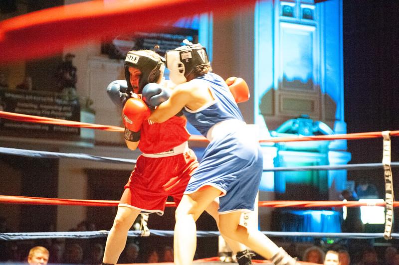 Alexis Bolduc (red trunks), of Hudson, N.H., battles Alyssa Kinahan-Dundas (blue trunks), of Boston, during Thursday's Golden Gloves match at Lowell Memorial Auditorium. (Sun / John Corneau)