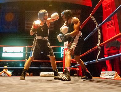 Gabriel Morales (black trunks) of Dracut, battles Kirby Espinal (grey trunks), of Dorchester, during Thursday's Golden Gloves match at Lowell Memorial Auditorium. (Sun / John Corneau)