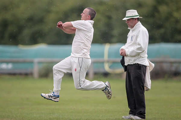 Masham bowler runs in, while it continues to drizzle.