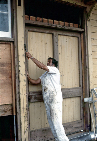 Painter's Union member prepares the building exterior. Note lettering over Baggage Room door.