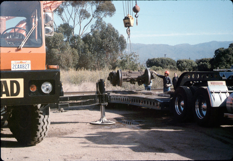 Caboose truck is lowered onto the awaiting truck trailer, 9/25/1986 acc2005.001.0622