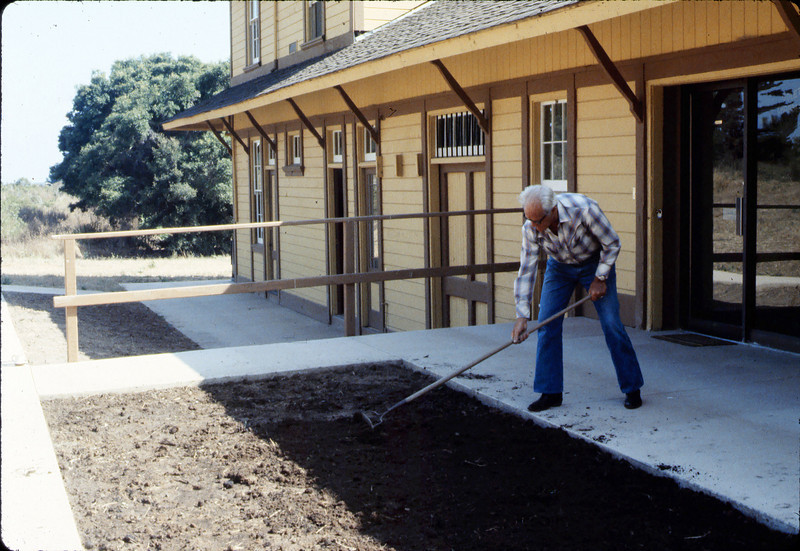 George Adams works on planter in front of Chamber of Commerce office, 7/1983. acc2005.001.0376