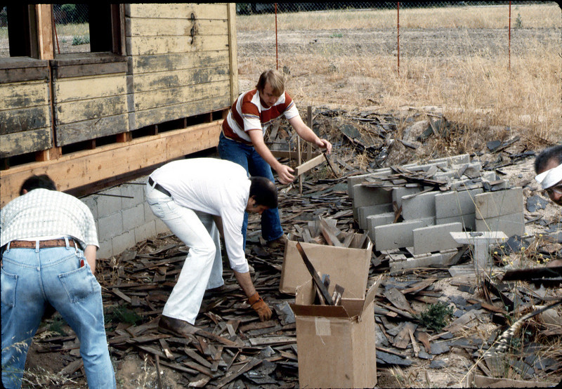 Volunteers pick up old shingles off ground, 6/1982. acc2005.001.0238