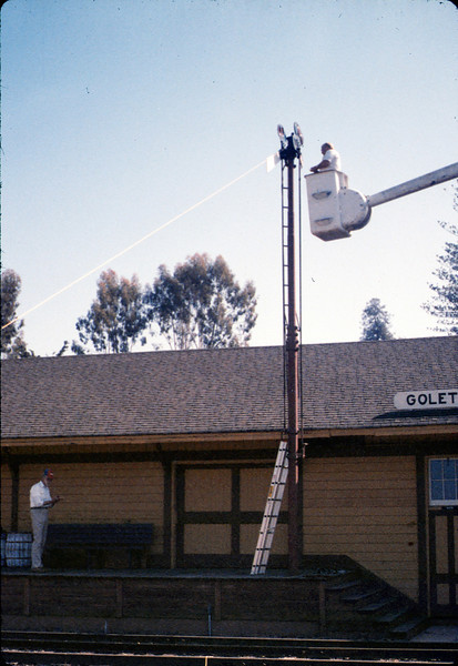 Bill Battisone, OK Tree Service, installs ladder on train-order pole, Work Day, 4/9/1988. acc2005.001.0923