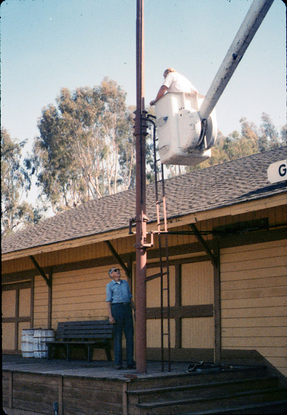 Bill Battisone, OK Tree Service, installs ladder on train-order pole while Gene Allen supervises, Work Day, 4/9/1988. acc2005.001.0920