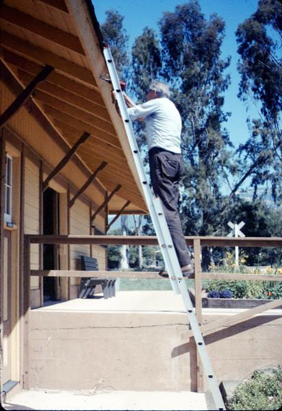 Gene Allen installs new redwood gutters, 5/1988. acc2005.001.0963
