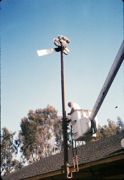 Bill Battisone, OK Tree Service, installs ladder on train-order pole, Work Day, 4/9/1988. acc2005.001.0919
