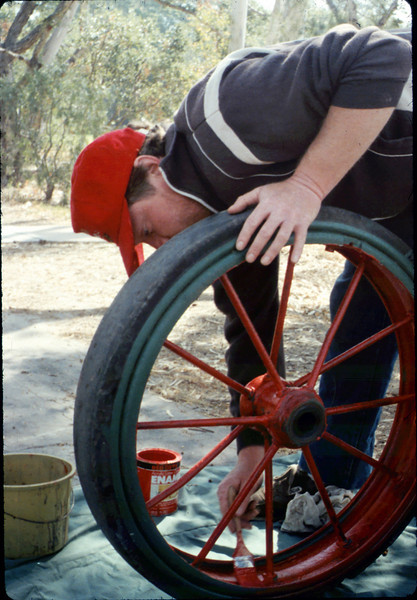Doug Conrow paints baggage cart wheel, Work Day, 4/9/1988. acc2005.001.0926