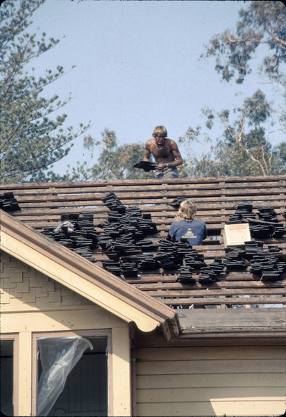 Fireman assists in roof-removal effort, 6/1982. acc2005.001.0234