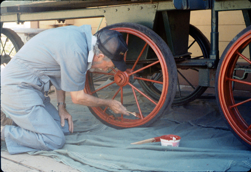 Malcolm Alexander paints baggage cart wheels, Work Day, 3/1988. acc2005.001.0917