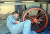 Malcolm Alexander paints baggage cart wheels, Work Day, 3/1988. acc2005.001.0918