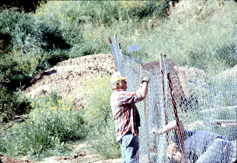 """Mover """"Harry"""" repairs the perimeter fence, 3/2/1982. acc2005.001.0184"""