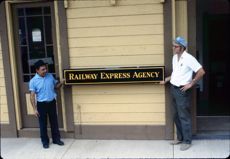 Former Goleta Depot agent Frank Vasquez and Ralph Moore pose with the Railway Express sign that once hung on the depot (see three wooden supports at top of image), 8/1983. acc2005.001.0399
