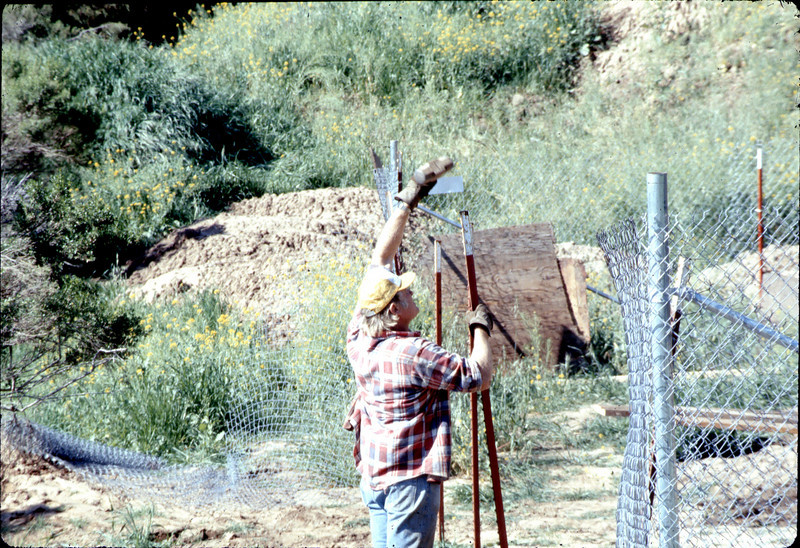 Harry repairs perimeter fence, 3/2/1982. acc2005.001.0187