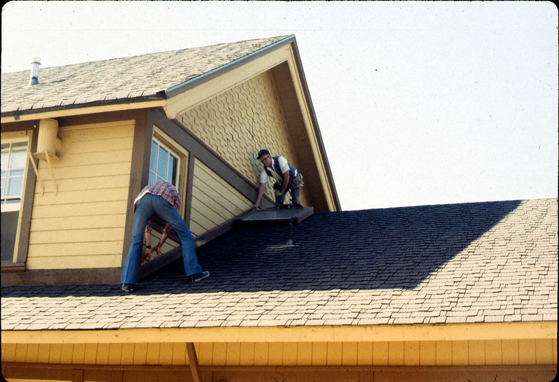 Ray Baird and Ralph Moore attaching board to depot roof, 1984. acc2005.001.0442
