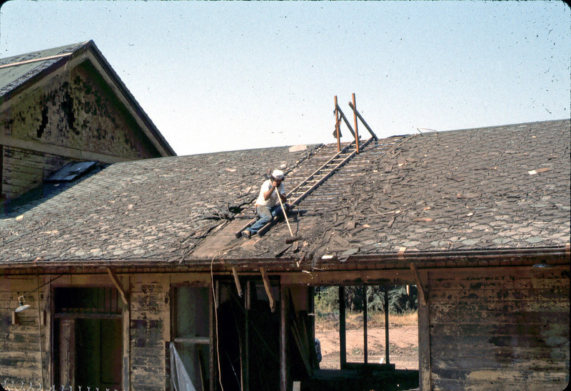 """Charlie"" removing shingles, 6/1982. acc2005.001.0219"