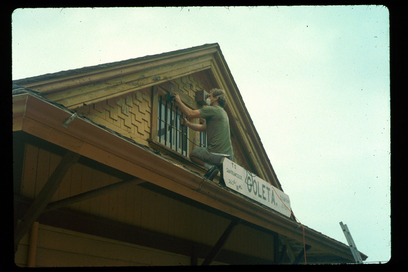 Prepping a north-end gable for re-painting, 1992. acc2005.001.1609