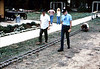 "Ralph Moore and Ray Baird inspect miniature-train track for first ""Depot Day"" event (Gene Allen on knees, right), 10/1983. acc2005.001.0417"