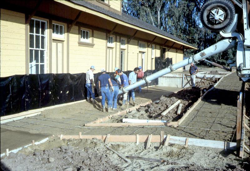 Pouring the perimeter sidewalks, 10/1982. acc2005.001.0341
