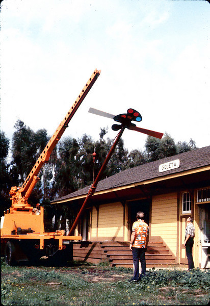 Specialty Crane & Rigging truck raises train-order pole for re-installation (Bill Everett, left, and Gene Allen are watching), 10/1983. acc2005.001.0425