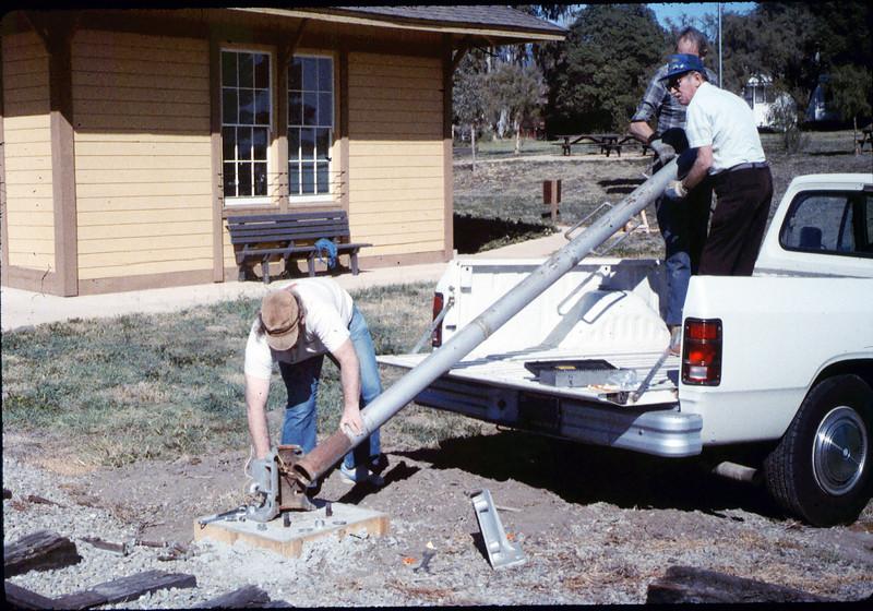 Gene Allen, Glen Apers and Glen's son install train-order post, 2/1987. acc2005.001.0687