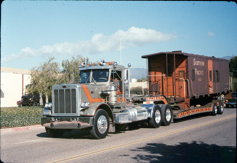 Caboose body is moved by truck (Dennis Romero Heavy Hauling) from La Patera to museum grounds, 9/25/1986 acc2005.001.0624