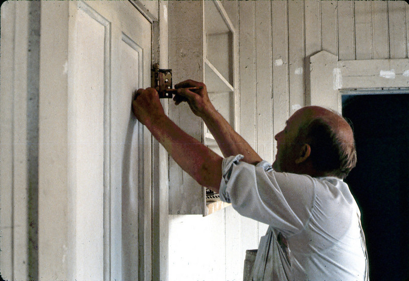 Ernest Thomsen rehangs a door upstairs, 7 or 8/1982. acc2005.001.0274