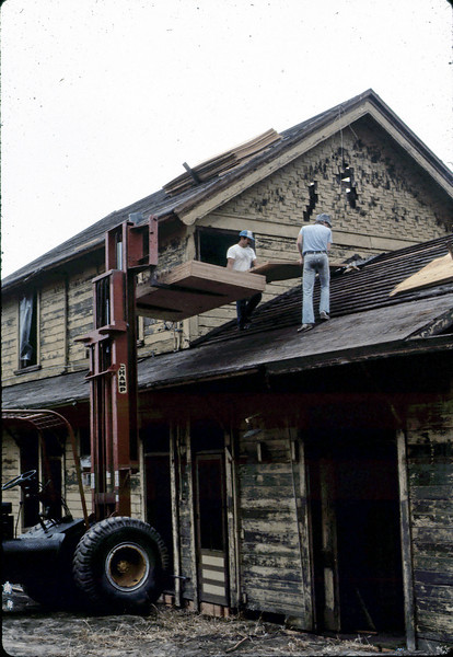 Worker and Bob Mowry (right), off load plywood for new roof, 6/1982 (photo out of sequence). acc2005.001.0267