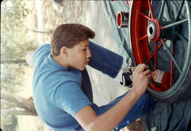 Steve Kramer paints baggage cart wheel, Work Day, 4/9/1988. acc2005.001.0927