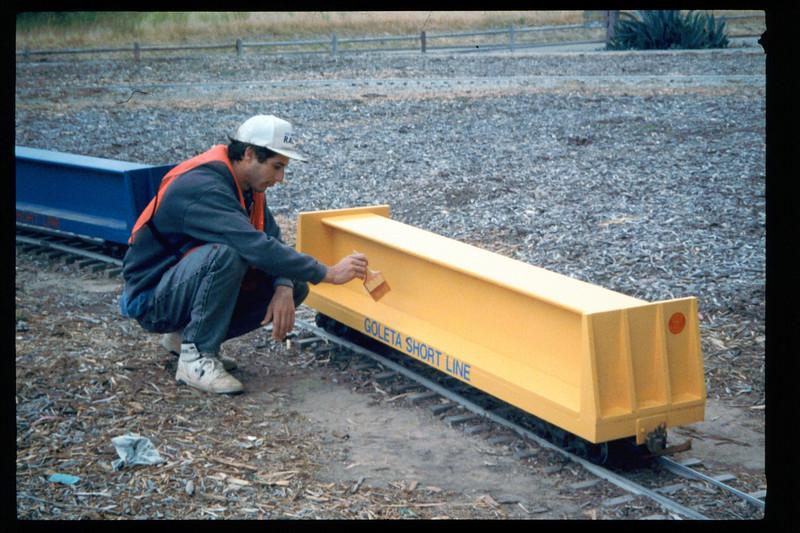 County SWAP worker paints miniature-train passenger cars, 1995. acc2005.001.2069